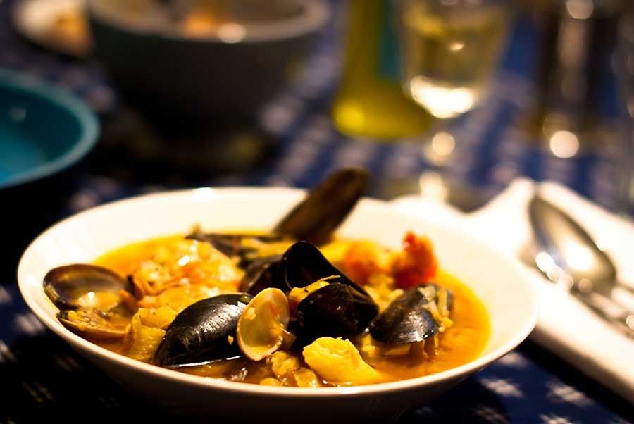 A bowl of fish soup with mussels, clams, etc