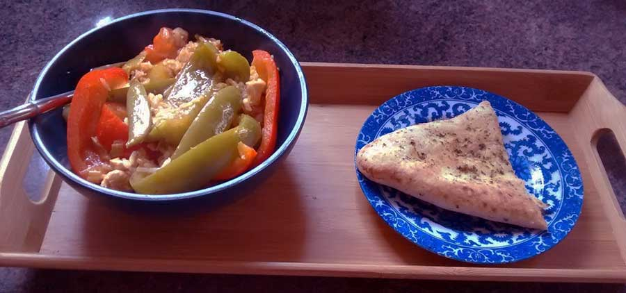 Bamboo tray holds a dish of Thai curry and half a naan bread.