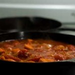 Pan of rich tomato sauce on the stove.