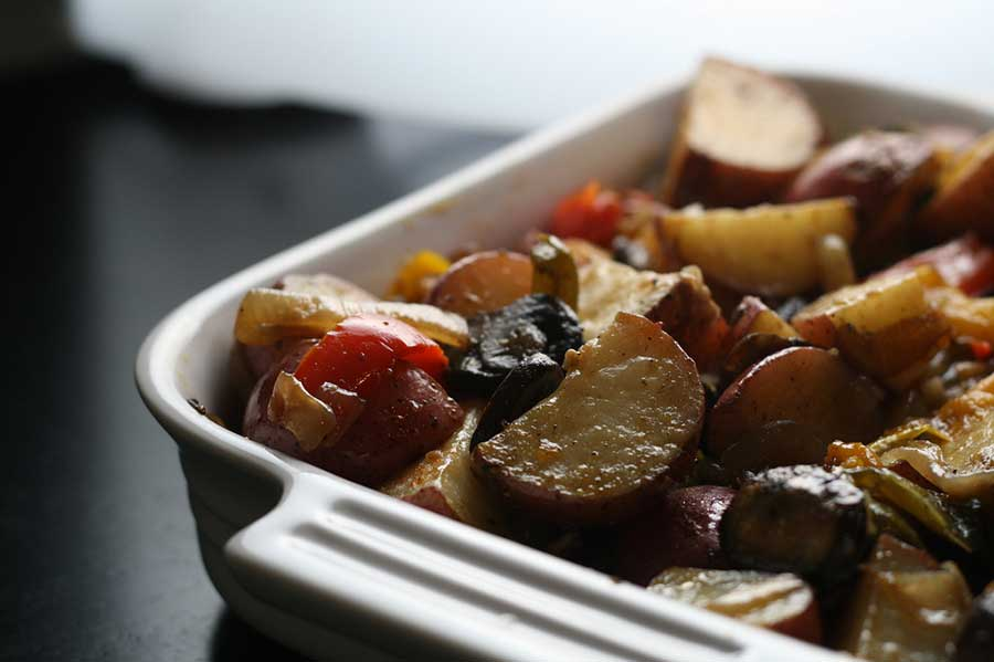 A white dish full of roasted potatoes and other vegetables.