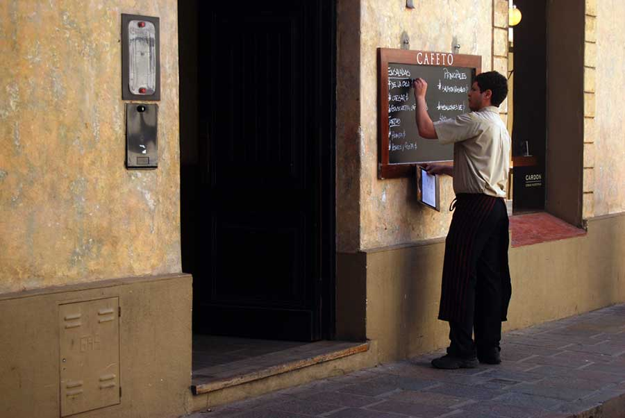 A waiter writes the daily menu on a blackboard outside a cafe.