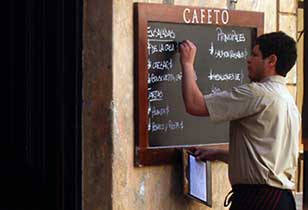 A waiter updates the daily menu on a restaurant blackboard.