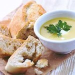 Bowl of roast celery and fennel soup along with a loaf of white crusty bread.
