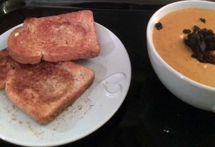 Bowl of soup with grilled black pudding scattered on top alongside a plate of toasted bread.