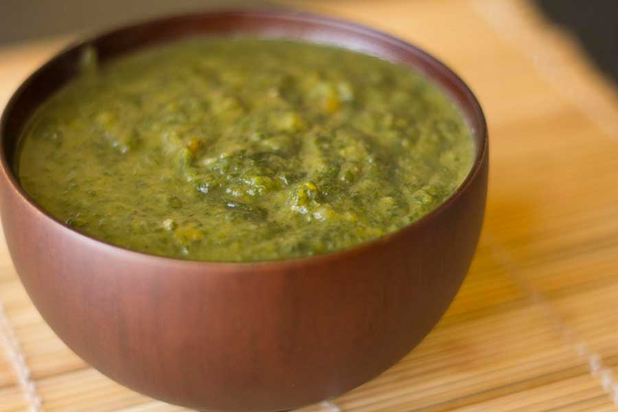 Polished wooden bowl of vibrant green spinach soup.