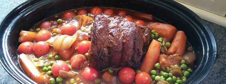 A jalfrezi coated beef brisket rests on a pan of vegetables